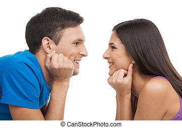 Loving couple. Beautiful young loving couple looking at each other and smiling while isolated on white