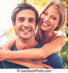 Loving couple. Beautiful young loving couple standing outdoors together while woman hugging her boyfriend and smiling