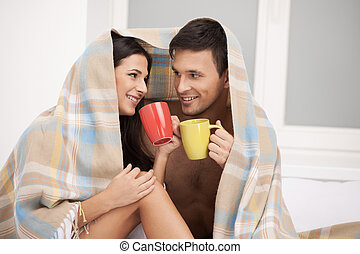 Loving couple. Beautiful young loving couple looking at each other and drinking coffee