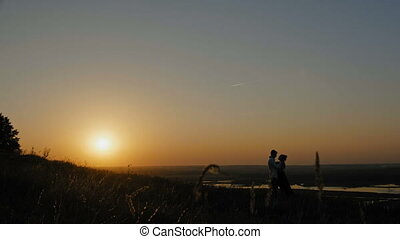 loving couple - brave young man and beautiful girl at sunset...