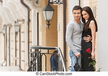 Loving couple. Cheerful young couple hugging while standing outdoors