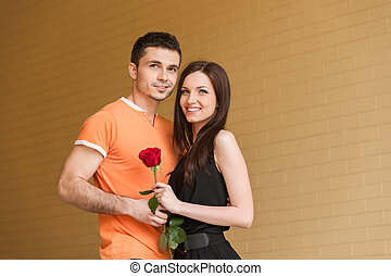 Loving couple. Cheerful young couple hugging while looking away and smiling