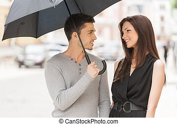 Loving couple. Cheerful young couple standing close to each other while man holding umbrella