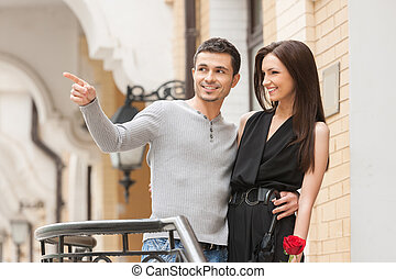 Loving couple. Cheerful young couple hugging while man pointing away and smiling