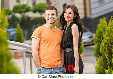 Loving couple. Cheerful young loving couple hugging and looking away
