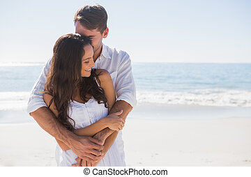 Loving couple cuddling - Loving couple cuddling at the beach...