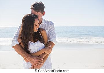 Loving couple cuddling - Loving couple cuddling at the beach...