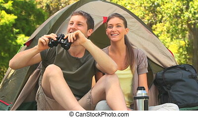 Loving couple doing camping - Couple sitting outside their...