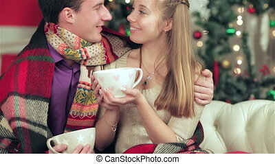 Young couple in love man and pretty girl wearing sweater and scarf at home