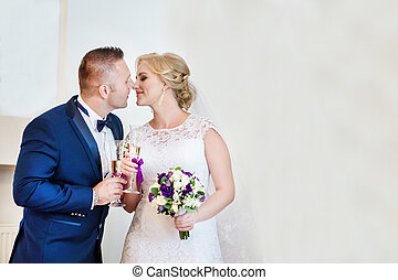 Loving couple drinking champagne in the registry office - A...