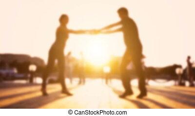 Loving couple enjoying dancing during sunset