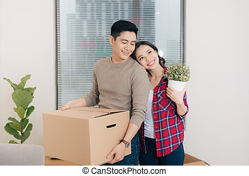 Loving couple enjoys a new apartment and keep the box in hands