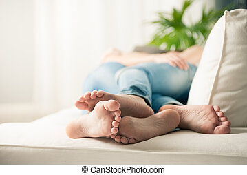Loving young lesbian couple embracing on sofa, feet close-up.