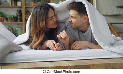 Loving couple girlfriend and boyfriend and lying in bed under blanket talking, laughing and kissing during happy weekend at home. Relationship and people concept,