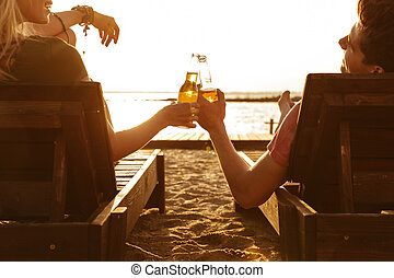 Loving couple have a rest outdoors on the beach drinking beer.