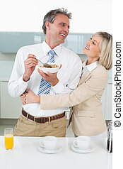 Loving couple having breakfast in kitchen
