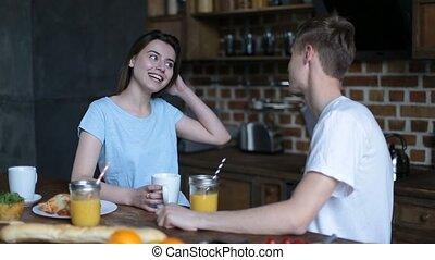 Loving couple having breakfast in modern kitchen