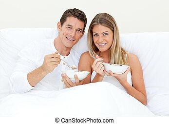 Loving couple having breakfast lying on their bed