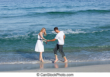 Loving couple having fun at the shore line at the beach