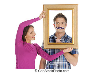 Loving couple having fun. Beautiful young woman holding a picture frame in front of her boyfriend face and smiling while isolated on white