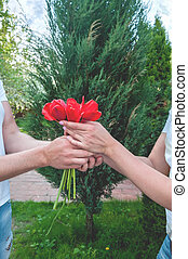 Loving couple holding a bouquet of tulips on a background of beautiful trees. A man gives his beloved flowers. The concept of expressing feelings of love