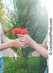 Loving couple holding a bouquet of tulips on a background of beautiful trees. A man gives his beloved flowers.