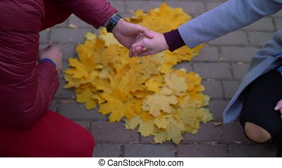 Loving couple holding hands over heart shape outdoors