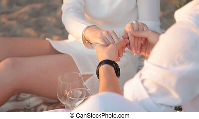 Loving couple holding hands sitting on the beach