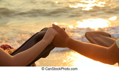 Loving Couple Holding Hands While Sitting On Outdoor Chairs At Beach