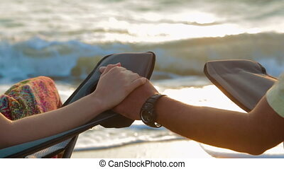 Loving Couple Holding Hands While Sitting On Outdoor Chairs At Seashore