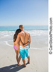 Loving couple hugging while looking at the sea