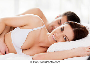 Loving couple in bed. Beautiful young loving couple lying in bed while woman looking at camera and smiling
