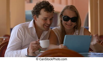 Loving couple in cafe with touchpad