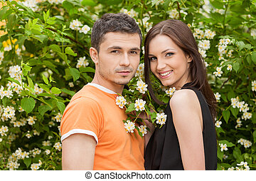 Loving couple in park. Cheerful young couple standing close to each other and looking at camera