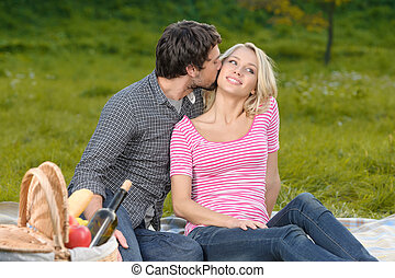 Loving couple in park. Loving young couple having a great time together on their intimate picnic