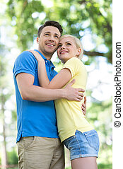 Loving couple in park. Low angle view of young loving couple hugging and looking away