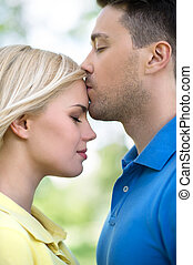 Loving couple in park. Side view of young handsome man kissing his girlfriend in park