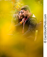 Loving couple in the autumn park sitting on a bench