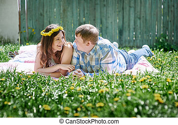 loving couple in the spring garden on a picnic blanket to lie