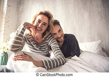 Waist up portrait of tender smiling spouse looking at camera. Man is gently putting head on woman shoulder while she is leaning to be closer to him. They are sitting on large white cot feeling happy