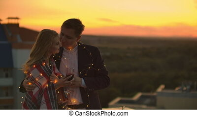 Loving couple is sitting on the roof of the house. In the ...