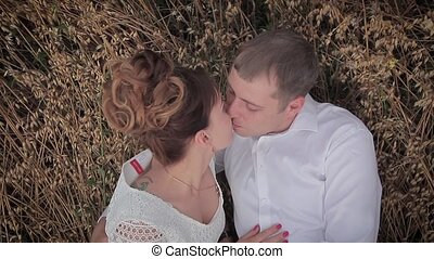Loving couple kisses. Lying on the grass