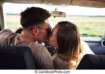 Loving couple kissing and embracing in a car
