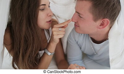 loving couple kissing under a blanket