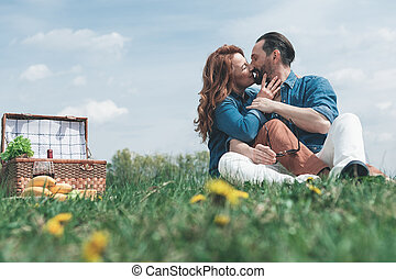 Loving couple kissing while resting in the nature