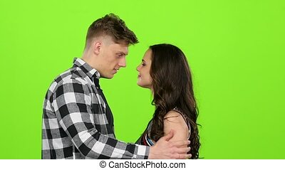 Loving couple look at each other and begin to kiss. Green screen. Slow motion