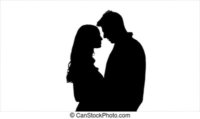 Loving couple look at each other and begin to kiss. Silhouette. White background. Slow motion