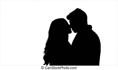 Loving couple look at each other and begin to kiss. Silhouette. White background
