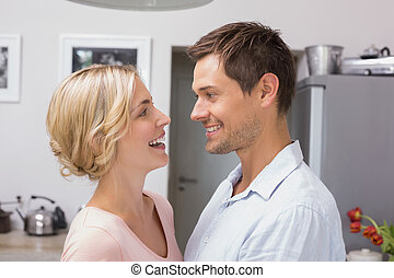 Loving couple looking at each other in the kitchen