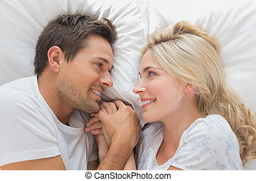 Loving couple looking at each other while lying in bed